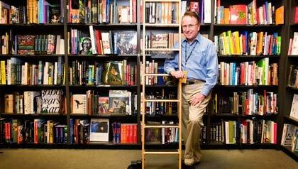 Empleos para personas mayores - Hombre en la estantería de una librería.