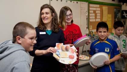 Jacobi Ann Brown, de 52 años, estudiante de enfermería, enseña nutrición a estudiantes de escuela intermedia.