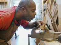 Kerry Hannon recommends five top small businesses to start when you are 50+- a carpenter works in his shop