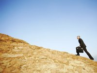 Businessman Climbing Rock