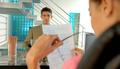 AARP tips how to create a winning resume- a woman conducts an interview with a resume in hand