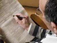 Imagen buscando empleo en los clasificados de un periódico, trabajos estacionales