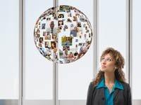 Empresaria con globo flotante de caras - Cuide su perfil de red social en la búsqueda de un puesto de trabajo