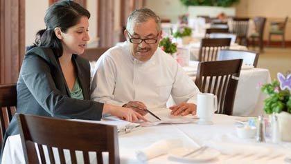 Propietario del un restaurante y su chef conversan sobre una mesa del restaurante - Planificar comercialización de la pequeña empresa