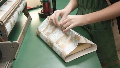 Mujer empacando un regalo en un mostrador - 12 grandes trabajos para estas vacaciones