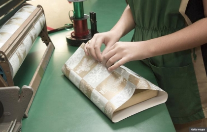 Woman gift wrapping at a retail counter, 12 Great Holiday Jobs (Getty Images)