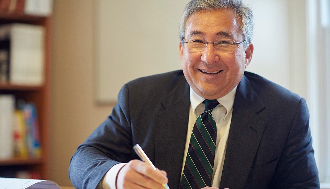 Ejecutivo sonriendo desde el escritorio de una oficina - 10 trabajos para mayores de 50