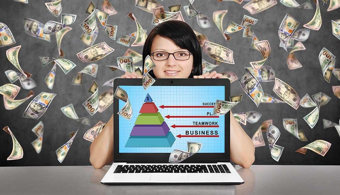 Mujer con una computadora y billetes de 100 dólares volando detrás de ella.