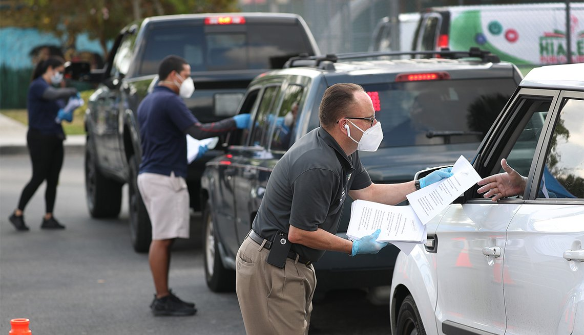 Eddie Rodriguez (R) and other City of Hialeah employees hand out unemployment applications to people in their vehicles