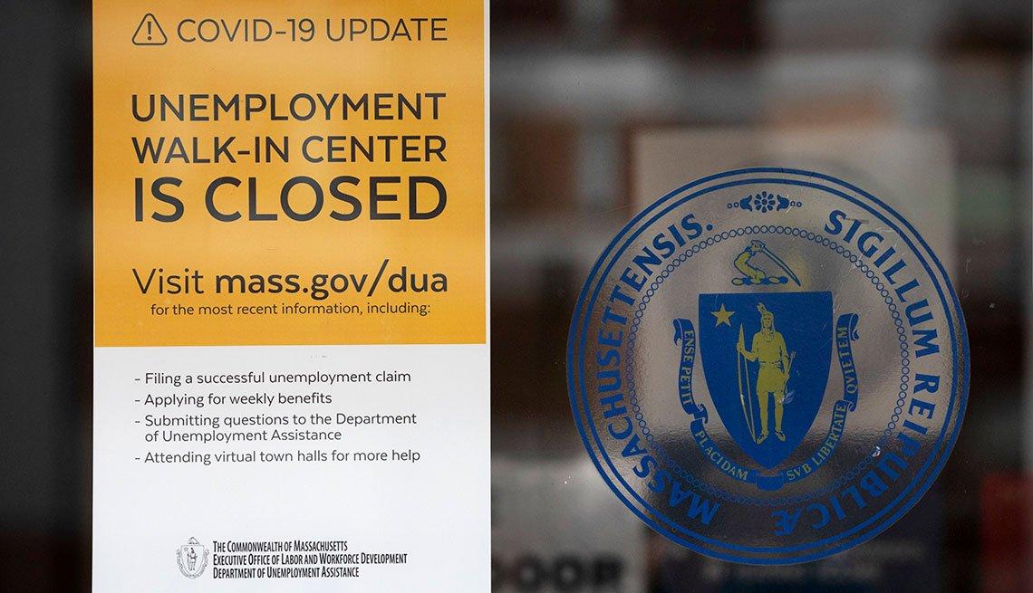 Centro de desempleo con un letrero en inglés que anuncia el cierre de la oficina y una página web para obtener información.
