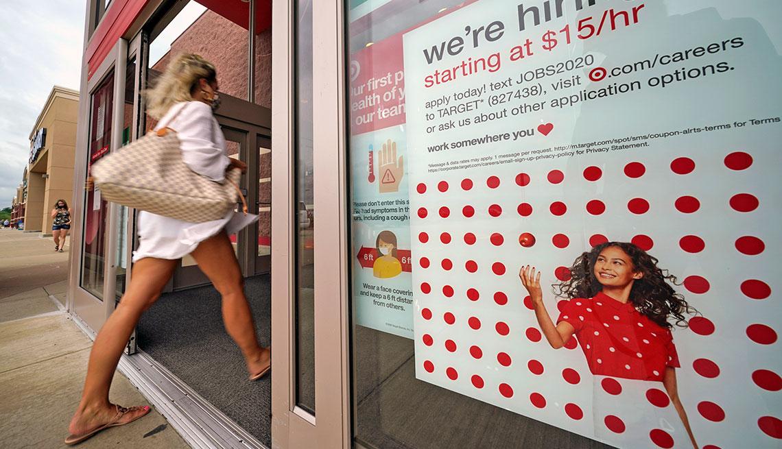 Mujer entrando a una tienda de Target, la cual anuncia en un aviso que están contratando nuevos empleados