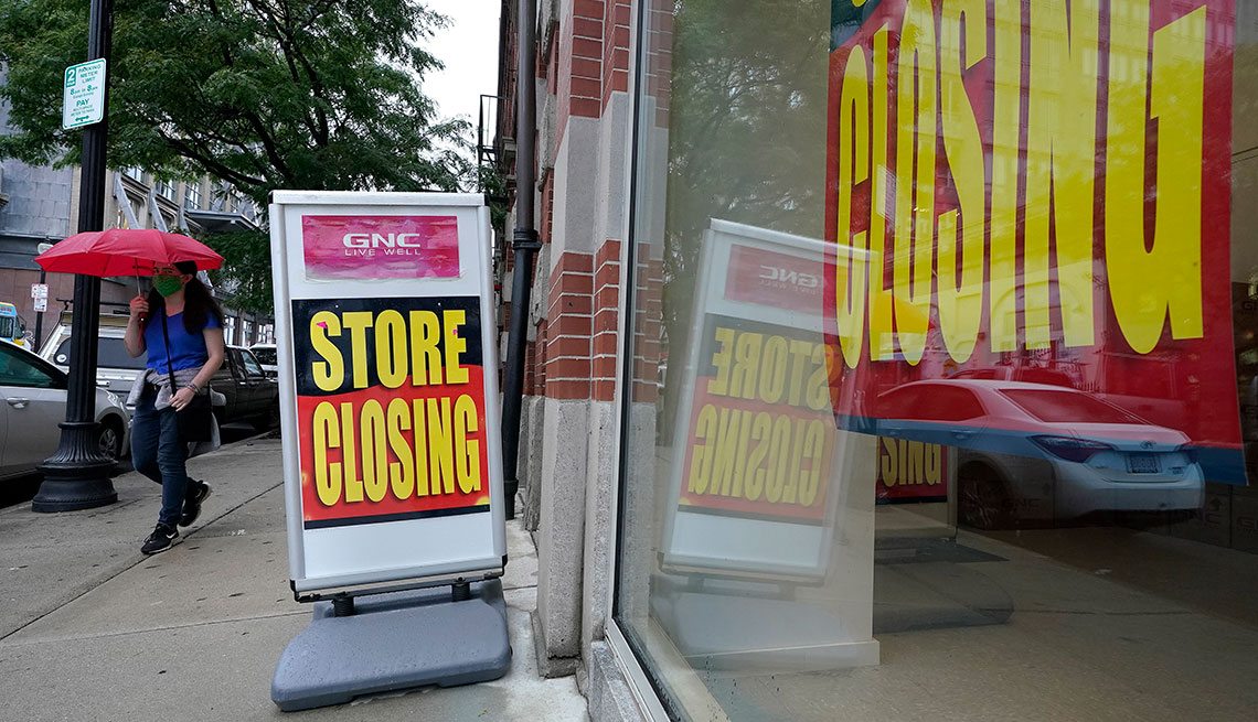 Vitrina de una tienda de GNC y una pancarta afuera que en inglés tienda en proceso de cierre.
