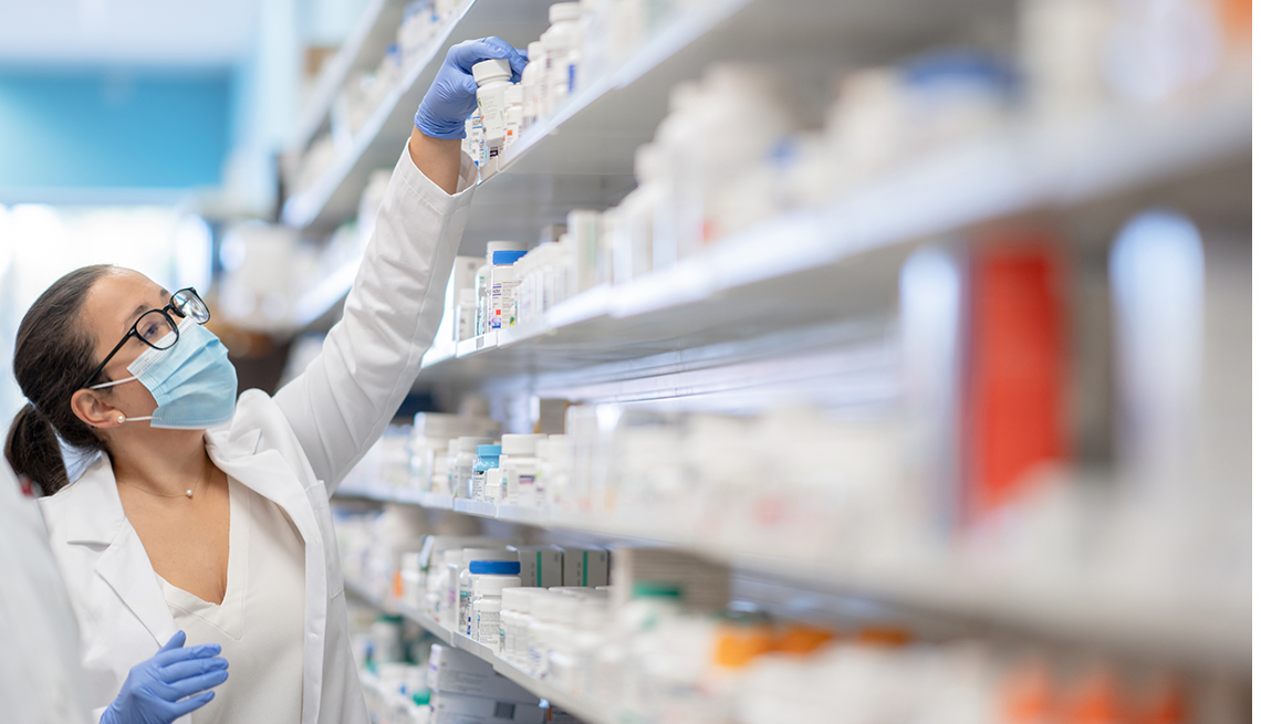 female pharmacy tech reaches for a bottle of medicine