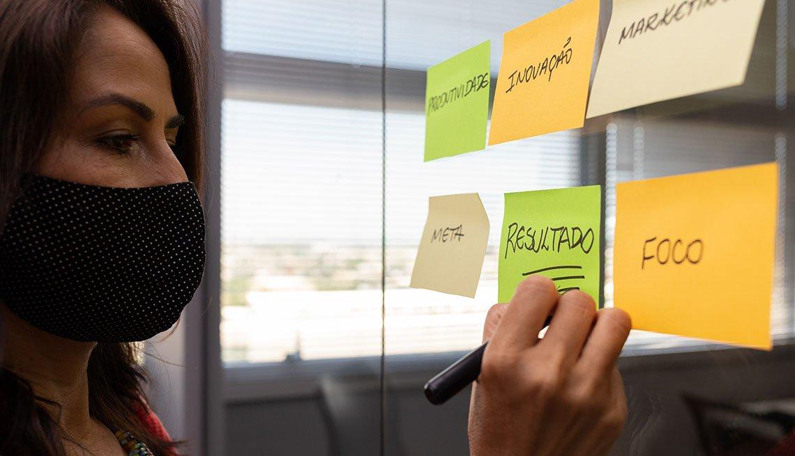 Mujer con mascarilla haciendo notas en papeles sobre un tablero.