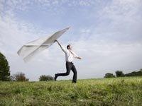 Hombre de negocios con un avión de papel gigante. - Requisitos para ser empresario.