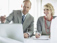 Man reviewing information on a lap while co-worker looks on, How to Find a Mentor