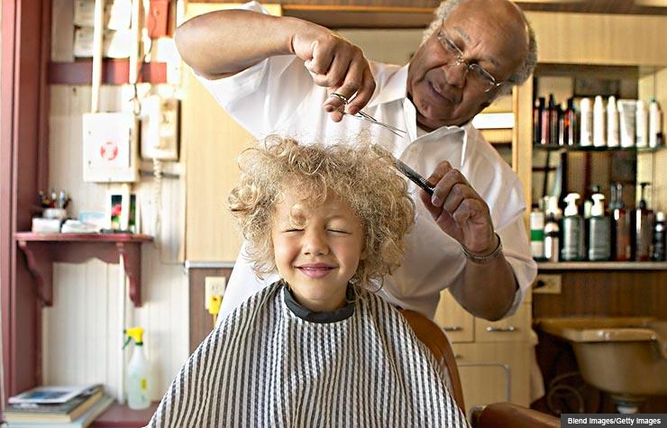 Barbero cortando el cabello a un  joven