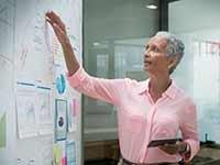 Mujer revisando proyecciones financieras sobre un tablero, trabajos con poco estrés, pero bien pagados