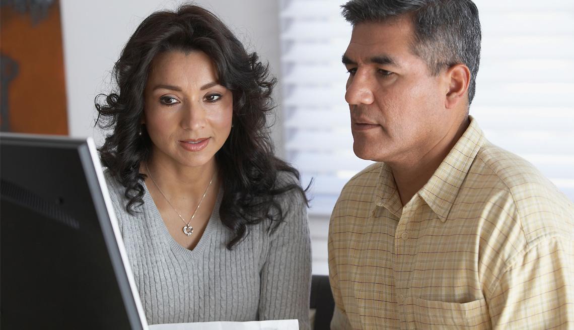Una pareja hispana frente a un laptop