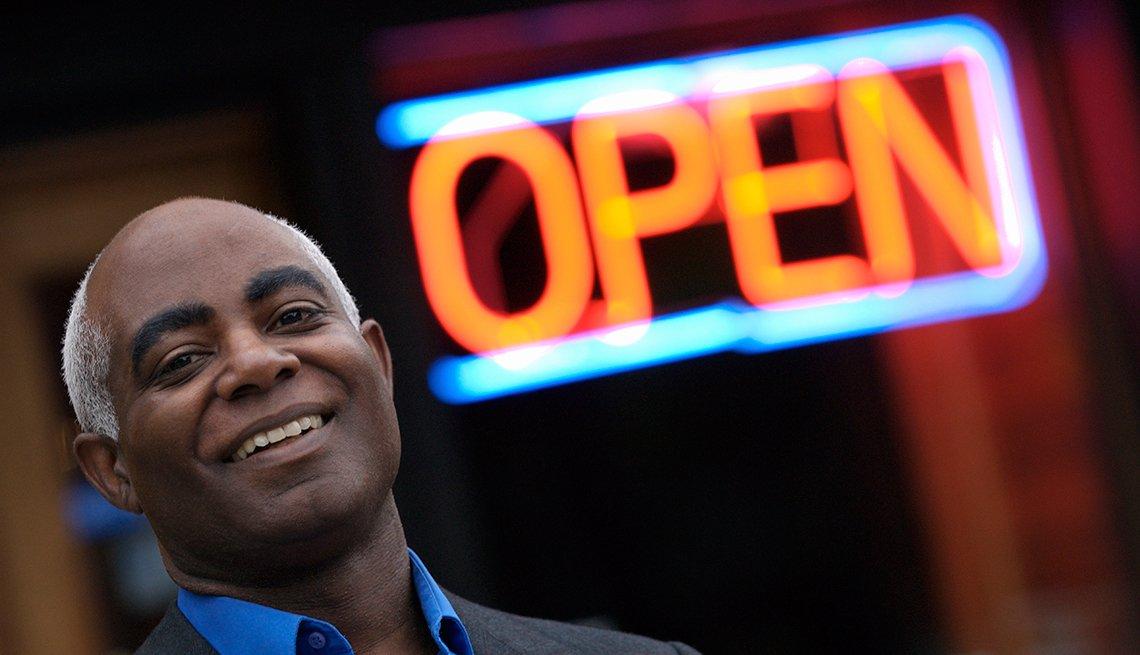 Hombre afroamericano frente a un signo en neon de Abierto (Open)