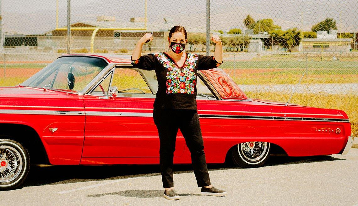 Darlene Tenes frente a un auto rojo.