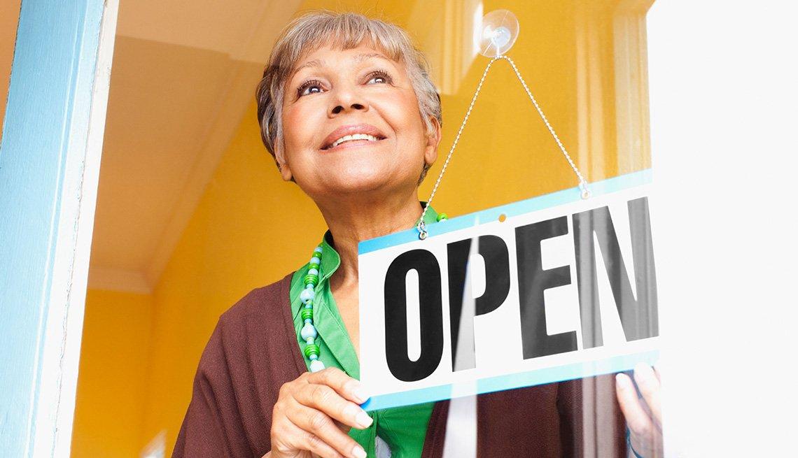 Mujer con una señal de su tienda abierta  frente a la puerta