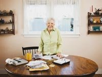 Senior woman smiles while standing at table covered by bills and calculators