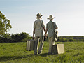 Senior couple in field with suitcases, tips on how to determine where to retire