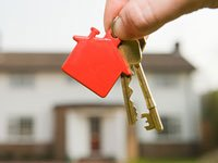 Hands dangling house keys in front of an out-of-focus house - Rent or Buy a Home