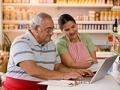 Hombre y mujer revisando las finanzas de un negocio frente a un computador - Comprar negocio