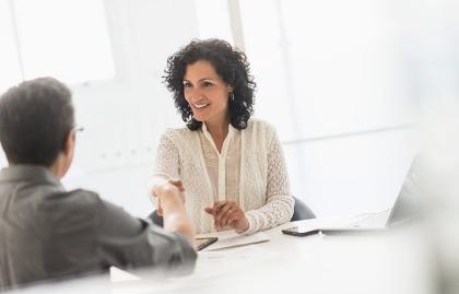 Un hombre y una mujer en una oficina dándose un saludo de manos - El nuevo sueño de la jubilación, seguir trabajando.