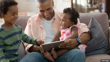 Padre y sus hijos en un sofá, beneficios del Seguro Social para los niños