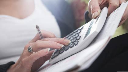 Mujer con calculadora, cuándo comenzar los beneficios del Seguro Social