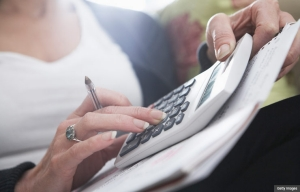 Woman holding calculator, when to start Social Security benefits