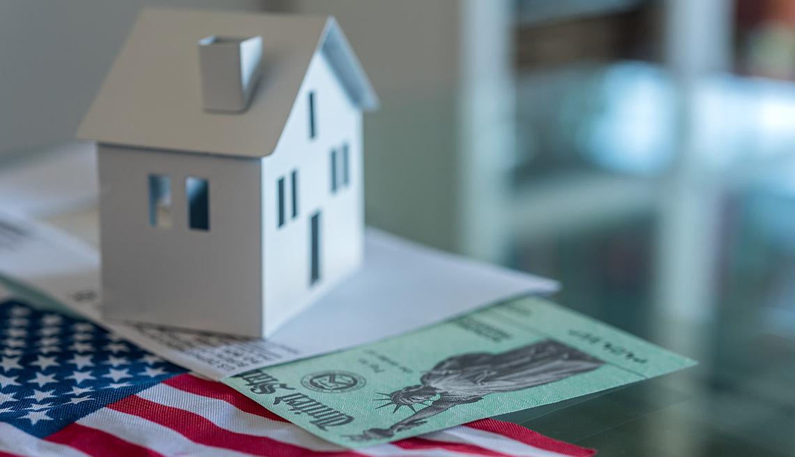 Modelo de una casa sobre una bandera de los Estados Unidos y cheque de estímulo del Departamento del Tesoro de los Estados Unidos