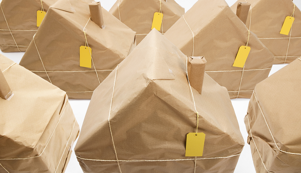 Model Houses Wrapped in Brown Paper, Tied With String, with Price Tags, selling real estate as a new career