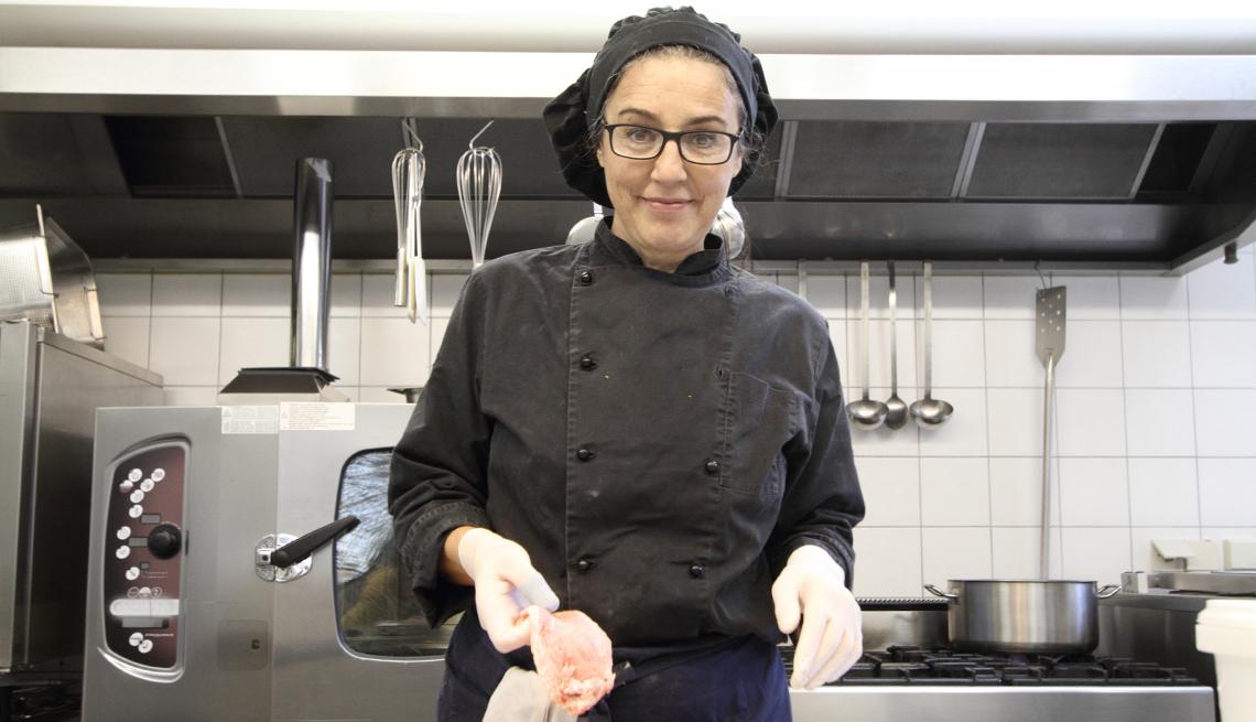 A woman prepares chicken breast in a restaurant kitchen
