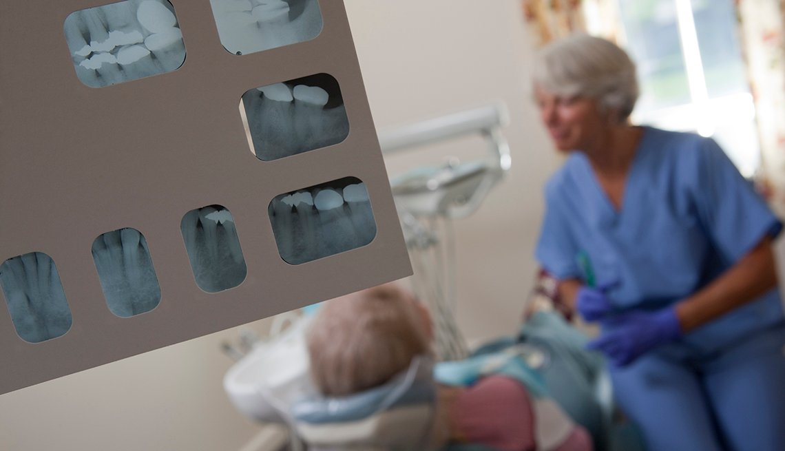 An X-Ray of a patient's dental work is shown in a room where a dental hygienist works with a patient