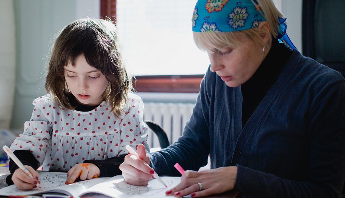 A teacher works on coloring with a young girl