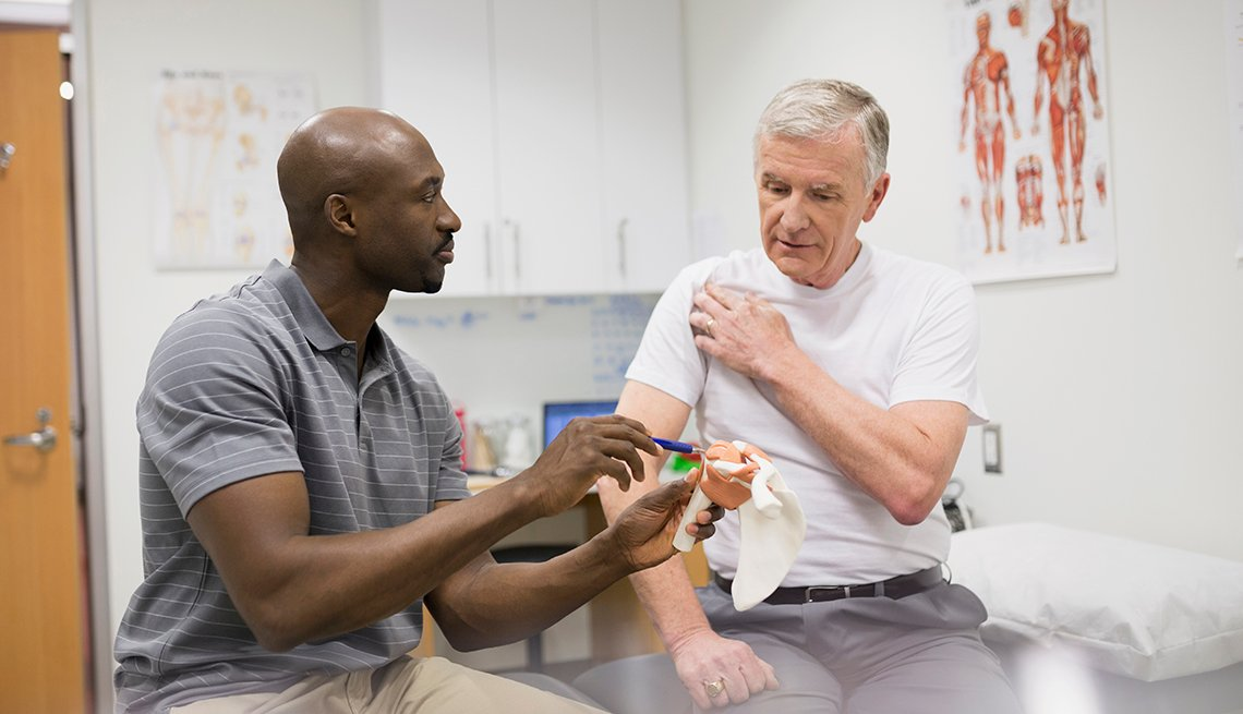 A male physical therapist treats a male patient with shoulder pain