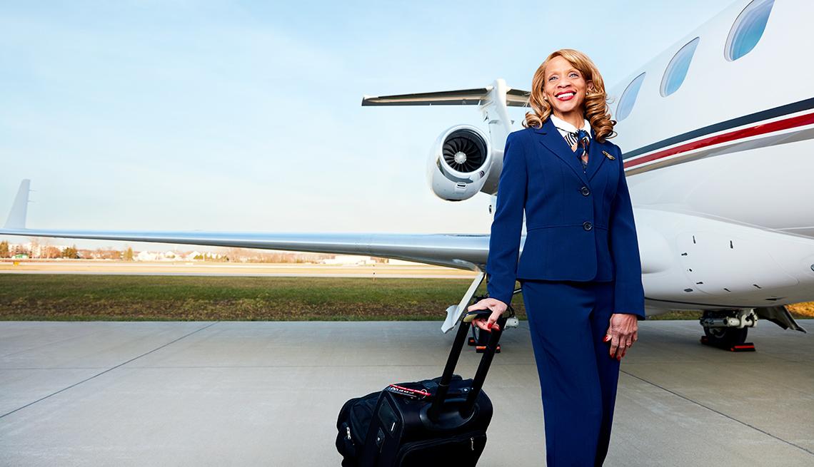 Flight Attendant Venetia Clark stands beside a jet