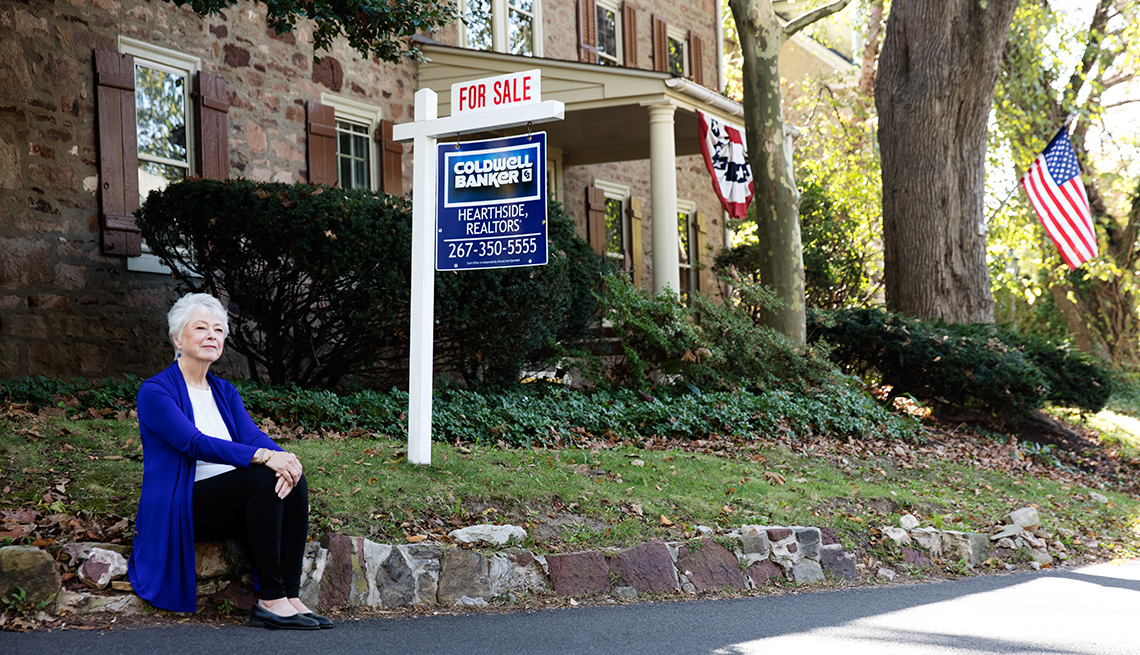 Real Estate Agent Joan Maguire sits on the curb in front of a house, near a For Sale sign
