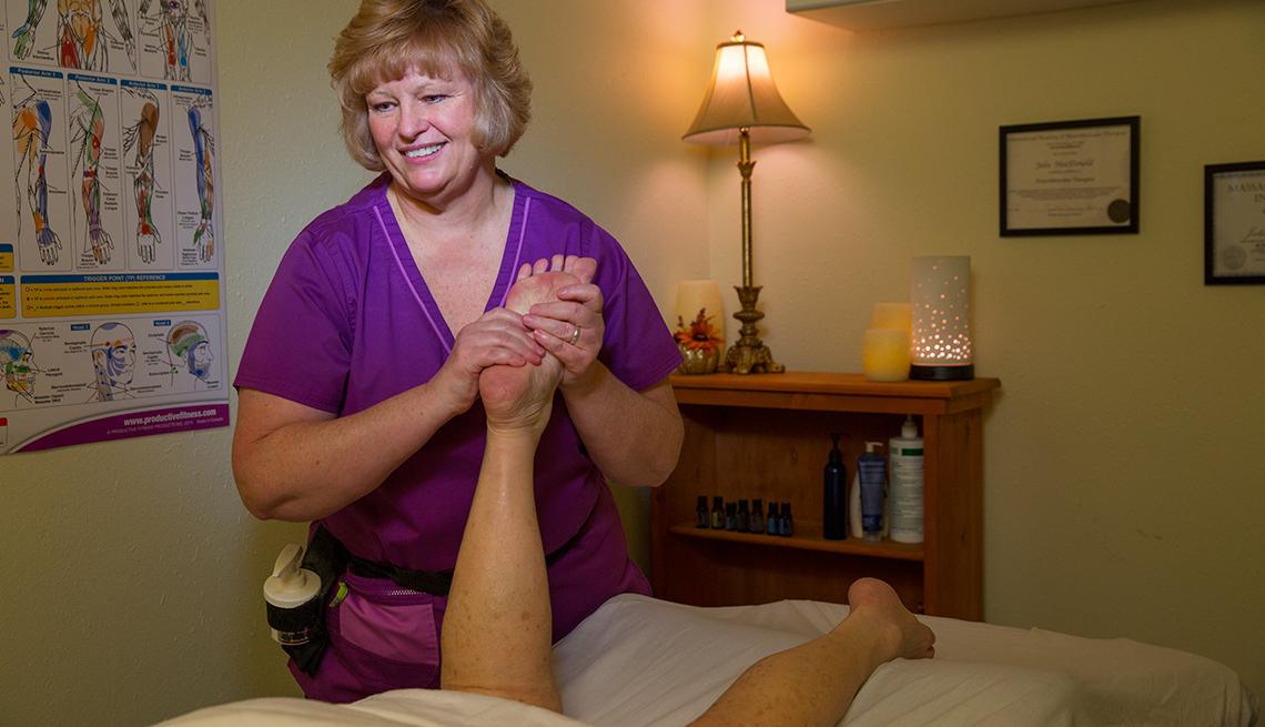 Massage therapist Julie MacDonald massages a client's foot