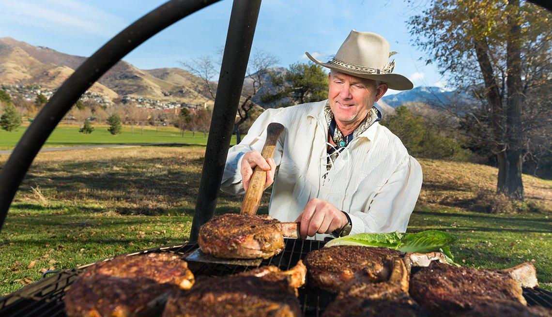 Mike Bertelsen flips a steak cooking over a cauldron
