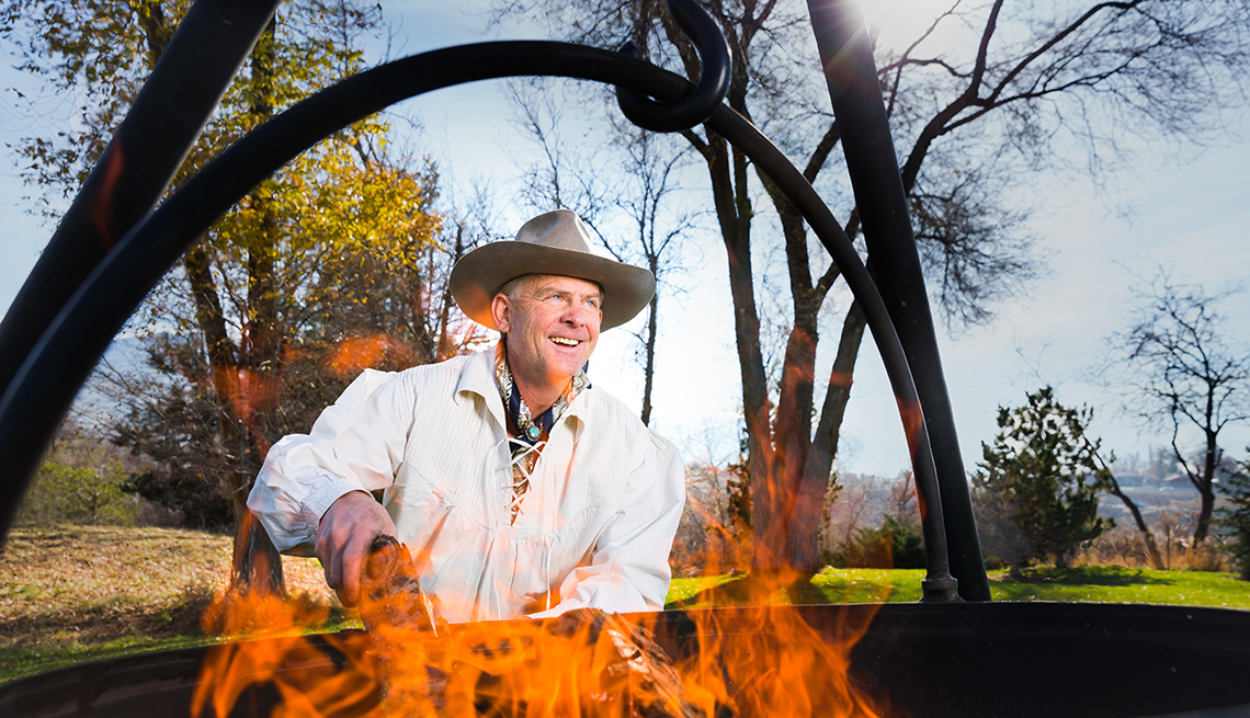 Mike Bertelsen, founder of Cowboy Cauldron, adds wood to a cauldron fire