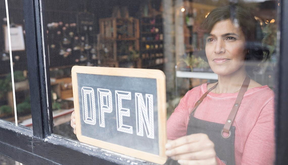 Female shop owner places an open sign on a window in her business