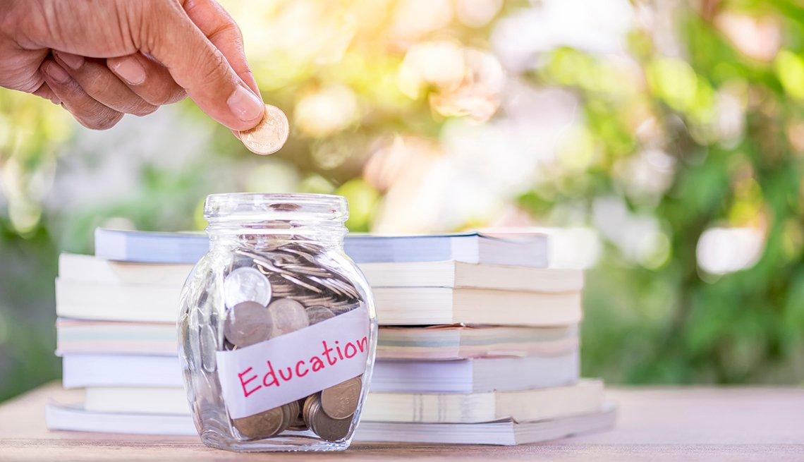Mano colocando una moneda en una jarra con el letrero educación