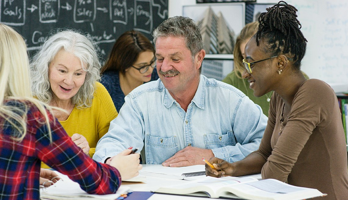 Group of adults sit around a table during a class at a college