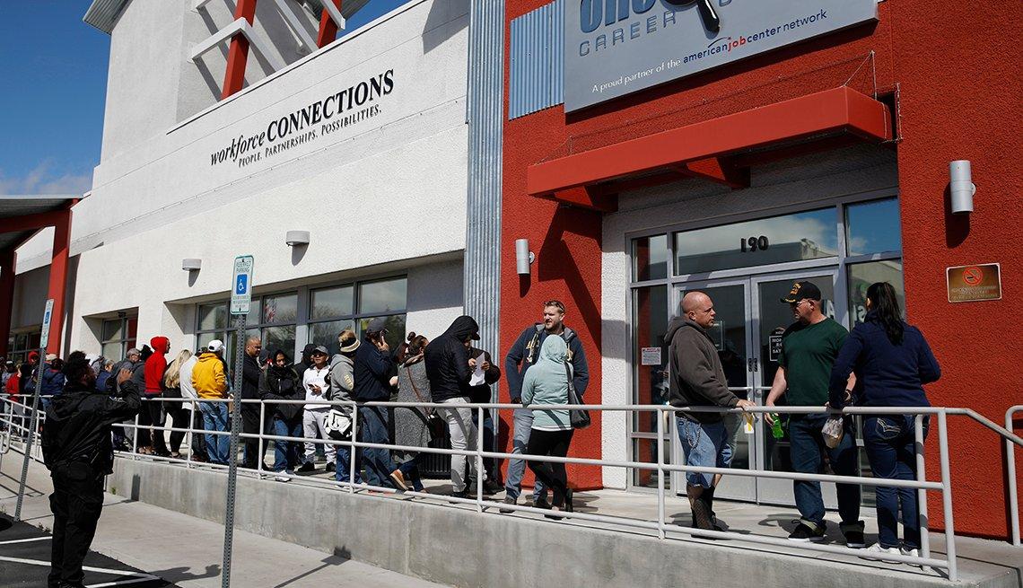 Personas esperando en una línea frente a un edificio.
