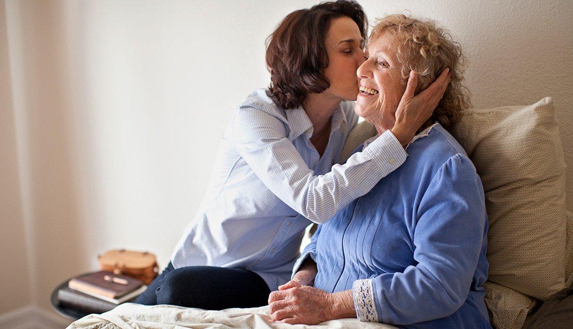 Mujer dándole un beso a una mujer mayor